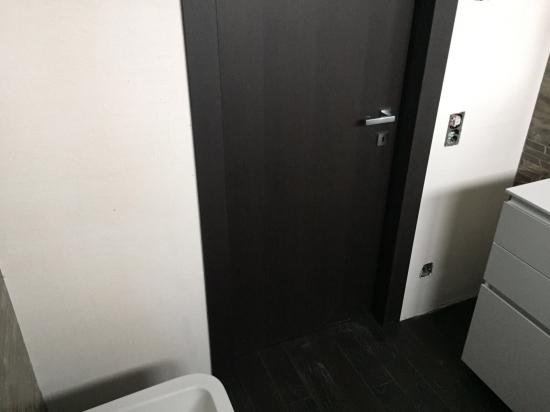 particolare di porta interna rivestita con lamella in rovere tinto wengè come il pavimento casa lavoro svolt